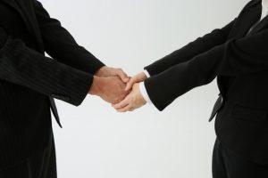 外回りの営業マンが両手で握手するイメージ